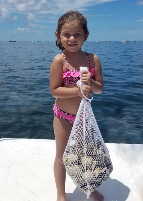 child holding bag of scallops on scallop charter